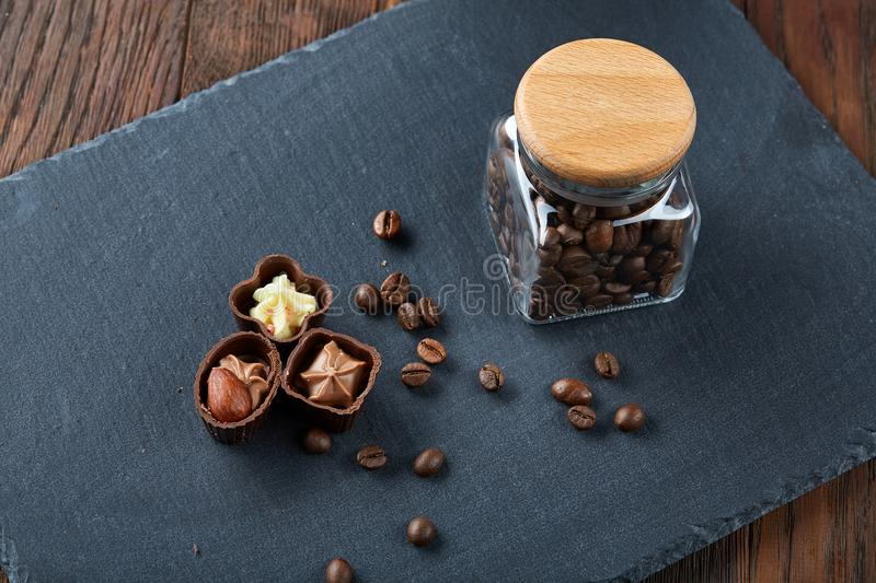 Side view of overturned glass jar with coffee beans and chocolate candies on wooden background, selective focus royalty free stock images