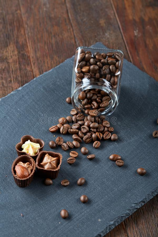 Side view of overturned glass jar with coffee beans and chocolate candies on wooden background, selective focus stock images