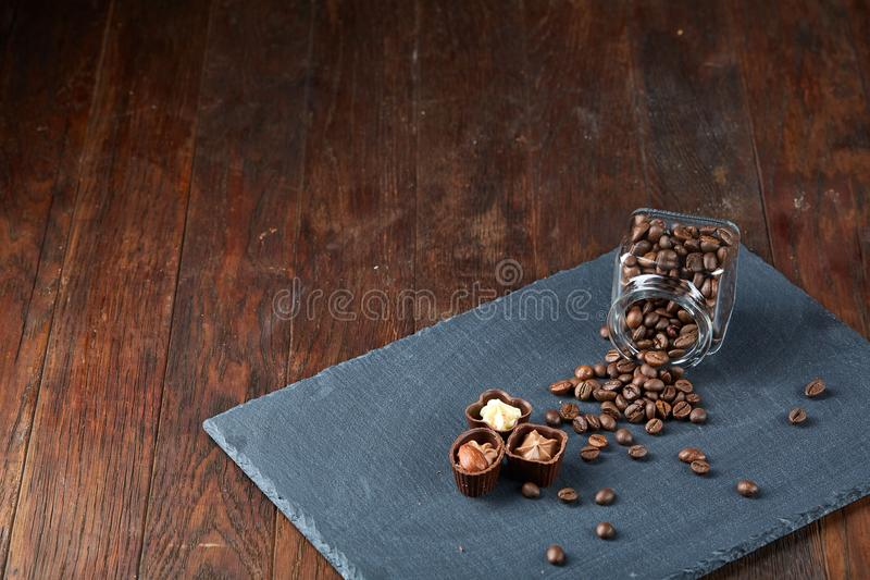 Side view of overturned glass jar with coffee beans and chocolate candies on wooden background, selective focus royalty free stock photography