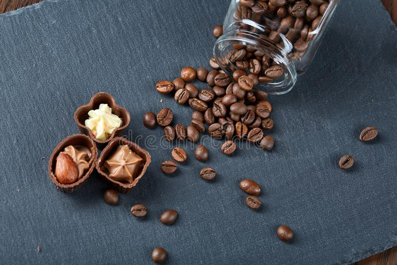 Side view of overturned glass jar with coffee beans and chocolate candies on wooden background, selective focus royalty free stock image