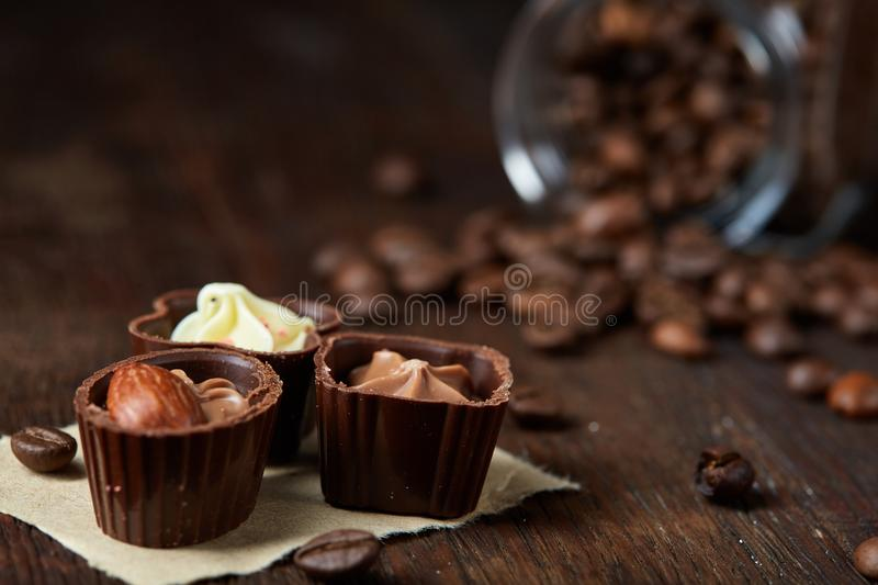 Side view of overturned glass jar with coffee beans and chocolate candies on wooden background, selective focus stock image