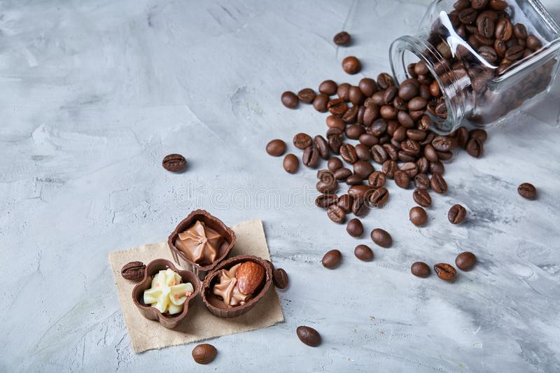 Side view of overturned glass jar with coffee beans and chocolate candies on wooden background, selective focus stock photography