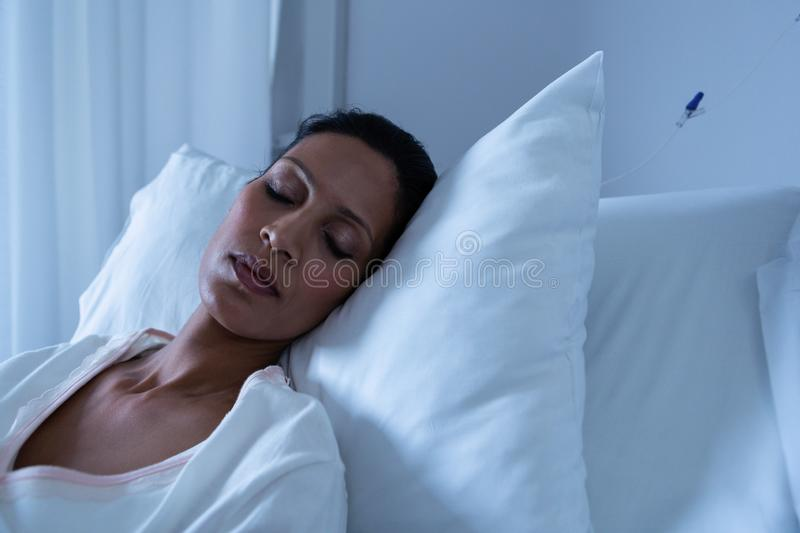 Female patient sleeping on bed stock image