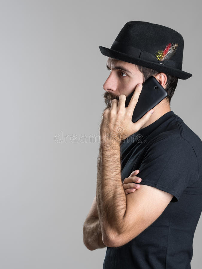 Side view of pensive bearded young man talking on the phone looking away. Over gray studio background royalty free stock images