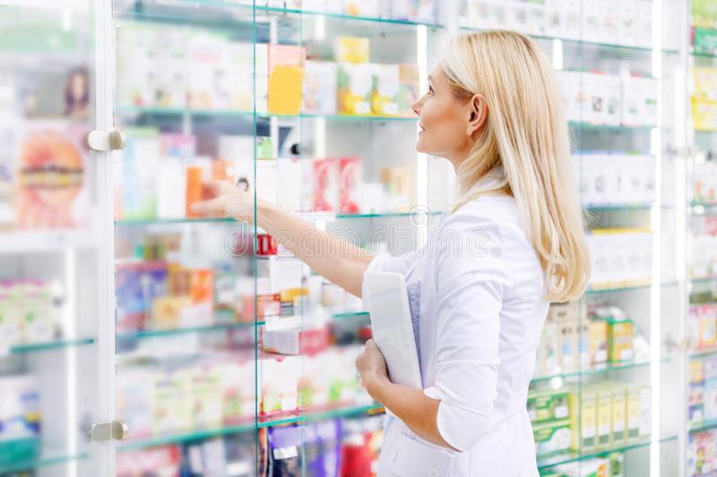 side view of pharmacist holding digital tablet and checking medications royalty free stock photo