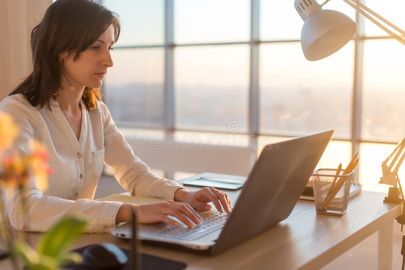 Side view photo of a female programmer using laptop, working, typing, surfing the internet at workplace. stock image