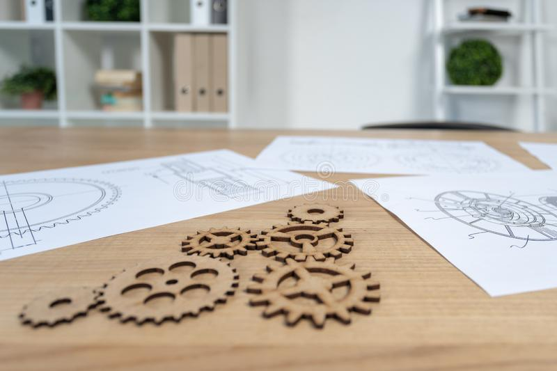 Side view photo of gear wheel on table. Selective focus on few cogwheel elements and detail. They lying at wooden desk in loft interior near technical drawing stock photos