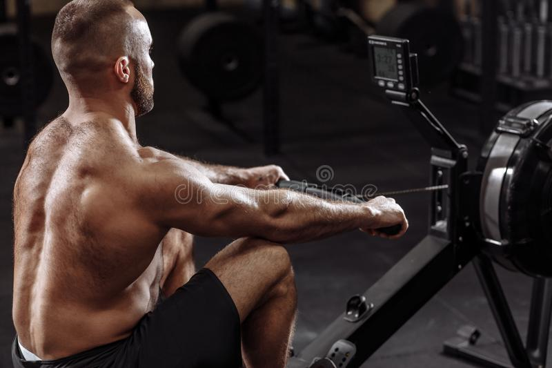 Side view photo of shirtles man using th rowing machine while training royalty free stock image