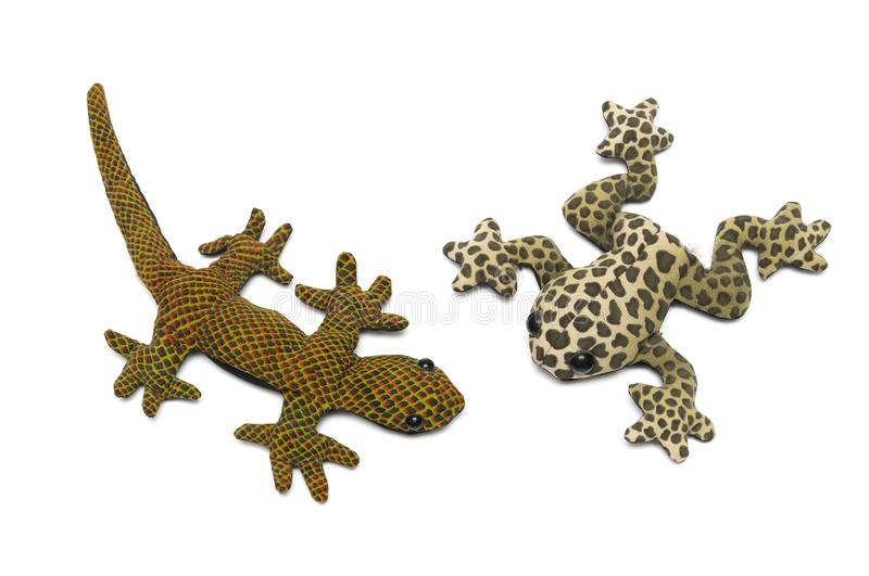 Stuffed toys of a light brown frog with dark brown spots and patches and a dirty green scaly gecko stock photos