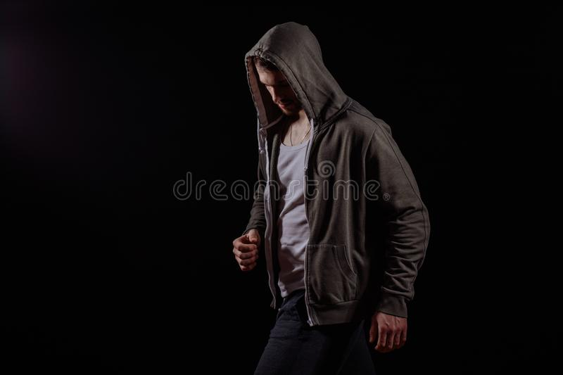 Side view photo of young bandit with bowerd head in hoodie. On the black background.running away gangster. closed nature. being along. thief royalty free stock images