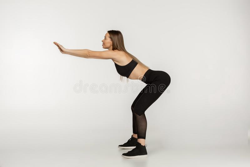Side view photo of young beautiful woman in black sportswear doing squat exersises royalty free stock photography