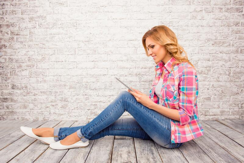 Side view photo of young girl sitting on floor with tablet.  royalty free stock image
