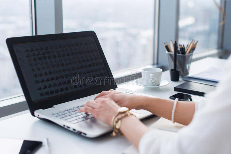 Side view picture of female hands typing, using pc in a light office. Designer working at workplace, searching new ideas stock photos