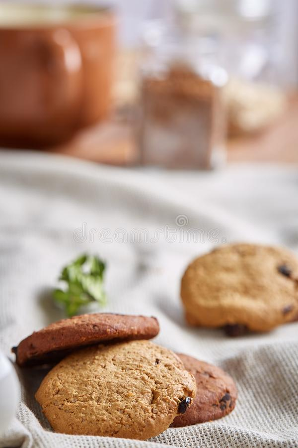Side view of a plate of chocolate chip cookies on a white plate on homespun tablecloth, selective focus stock photos