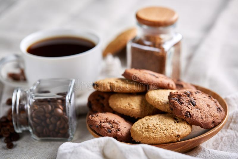 Side view of a plate of chocolate chip cookies on a white plate on homespun tablecloth, selective focus royalty free stock photo