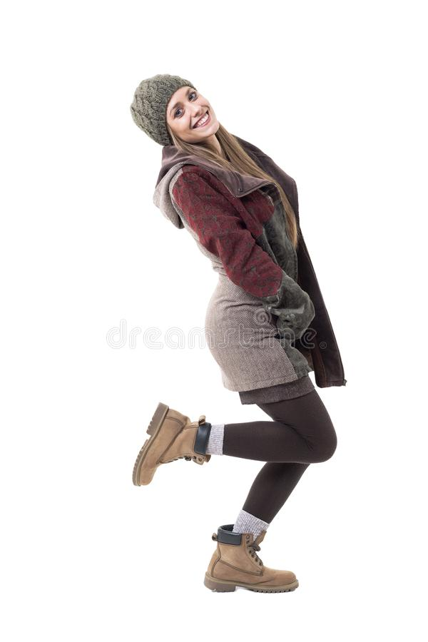 Side view of playful happy woman in warm winter clothes posing on one leg royalty free stock photography