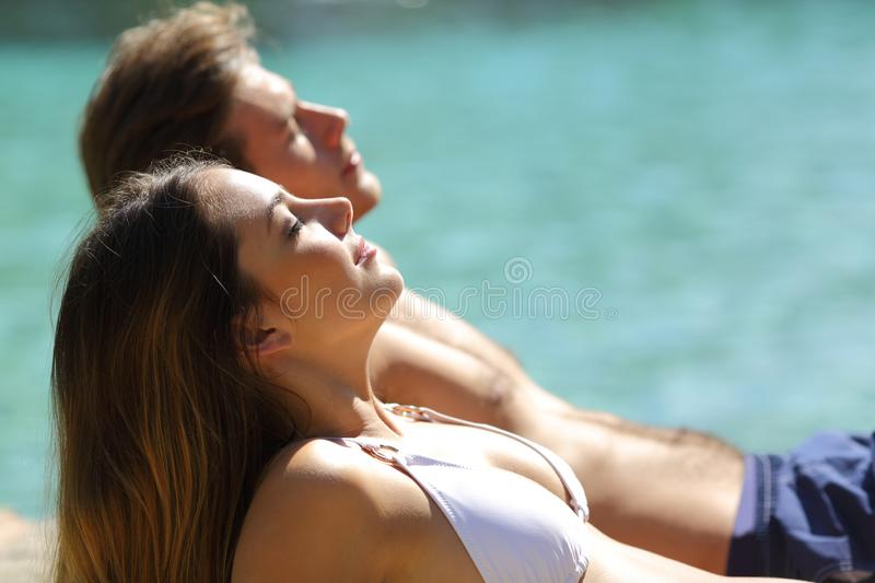 Relaxed couple sunbathing on the beach on vacation stock images