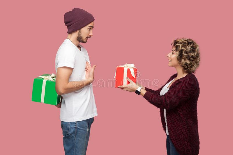 Side view portrait of amazing couple of friends in casual style standing, girl giving present box, boy hide behind gift, celebrate royalty free stock images