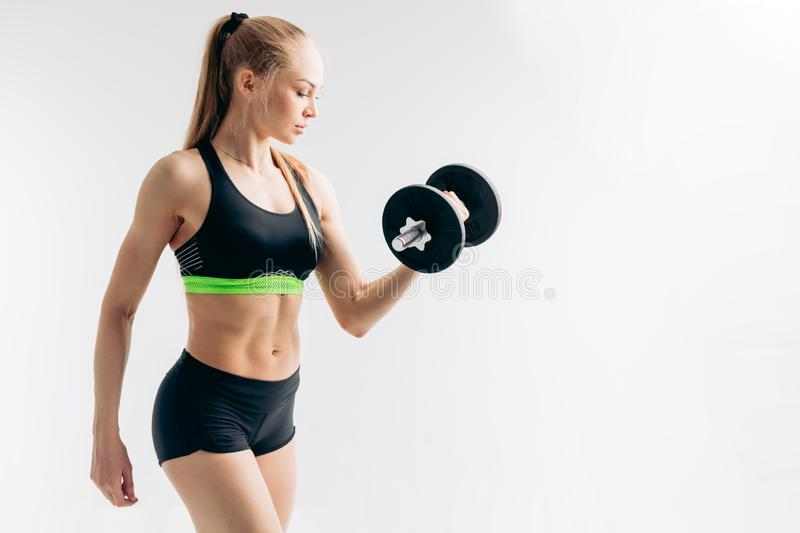 Side view portrait of a beautiful fair-haired young sportswoman doing exercises stock images
