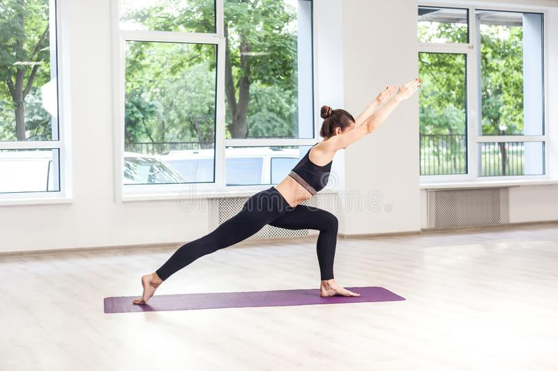 Side view portrait of beautiful young woman wearing in black pants and top working out against window, doing yoga or pilates. E view portrait of beautiful young stock photo