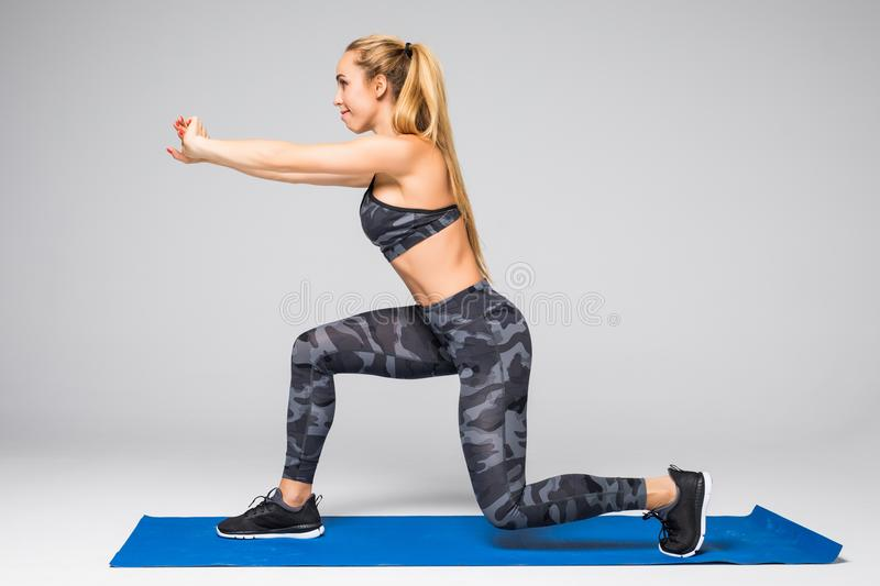 Side view portrait of beautiful young woman working out against grey wall, doing yoga or pilates exercise on gray stock photography
