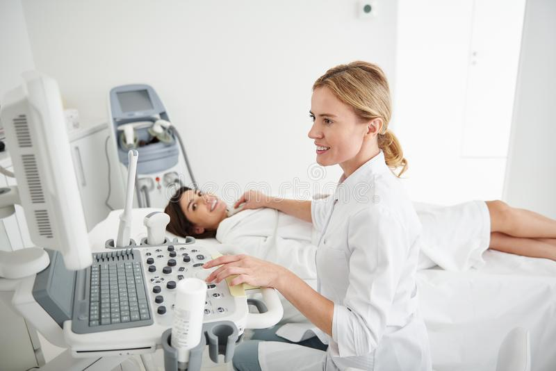 Young doctor using ultrasound scanner and examining thyroid of young lady. Side view portrait of charming physician in white lab coat looking at monitor of stock image