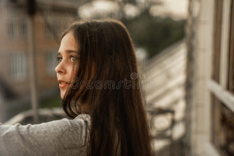 Side view portrait of cheerful young girl with long brunette hair looking away stock photo