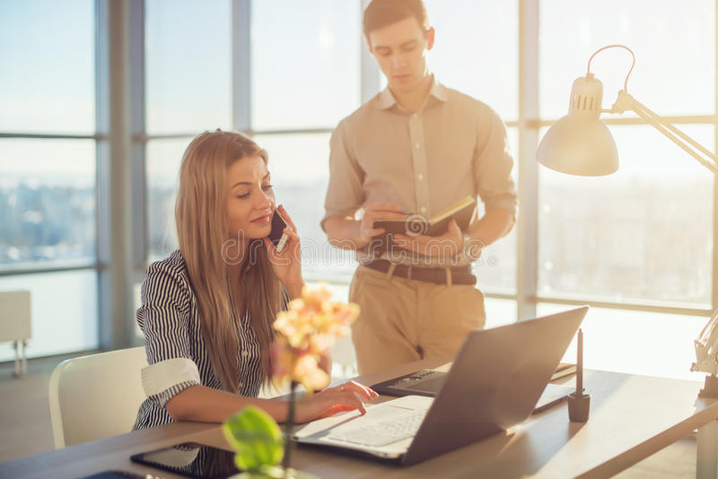 Side view portrait of colleagues in light spacious office busy during working day. Businesswoman planning schedule royalty free stock images