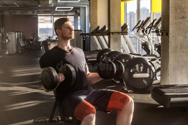 Side view portrait of concentration young adult man handsome athlete working out in gym, sitting on a bench and holding two. Dumbbell with raised arms, doing royalty free stock image