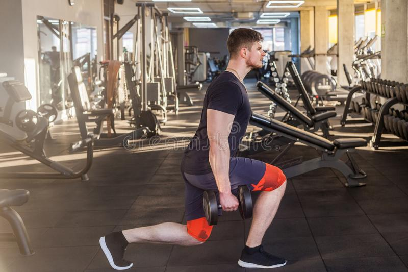 Side view portrait of concentration young adult sport man athlete working out in gym, standing on the knees and holding two. Dumbbells, doing exercises for legs royalty free stock image