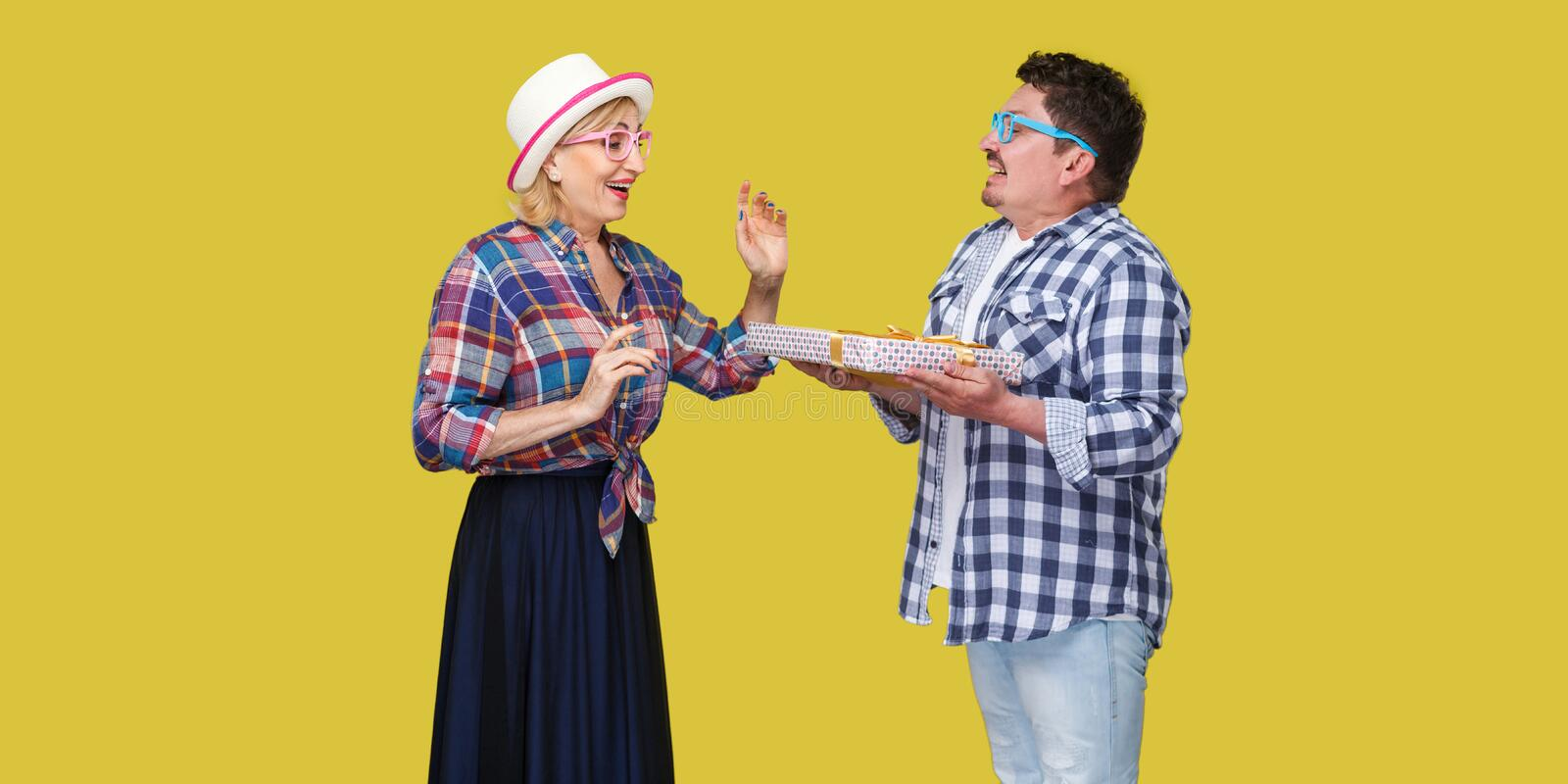 Side view portrait of couple of happy friends, man and woman in casual checkered shirt standing and husband giving present gift stock images