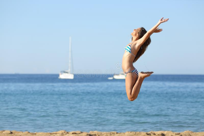 Excited woman in bikini jumping on the beach stock photos