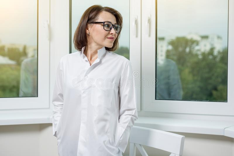 Side view portrait of female doctor looking out the window in a modern hospital or medical center stock images
