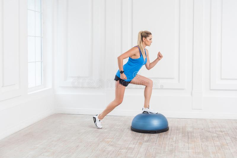 Side view portrait of focused sporty young athletic blonde woman in black shorts and blue top working in gym doing exersice in. Bosu balance trainer, making one royalty free stock photos