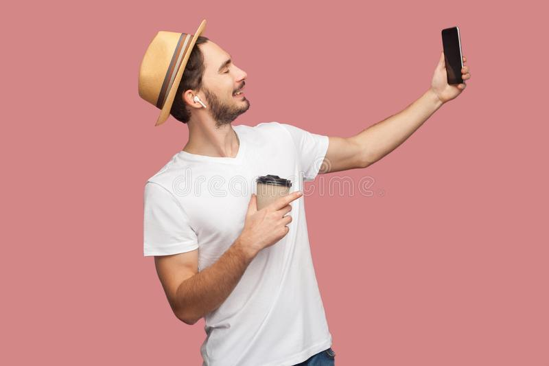 Side view portrait of handsome bearded young hipster man in white shirt and casual hat posing and making selfie photo with smile, stock images