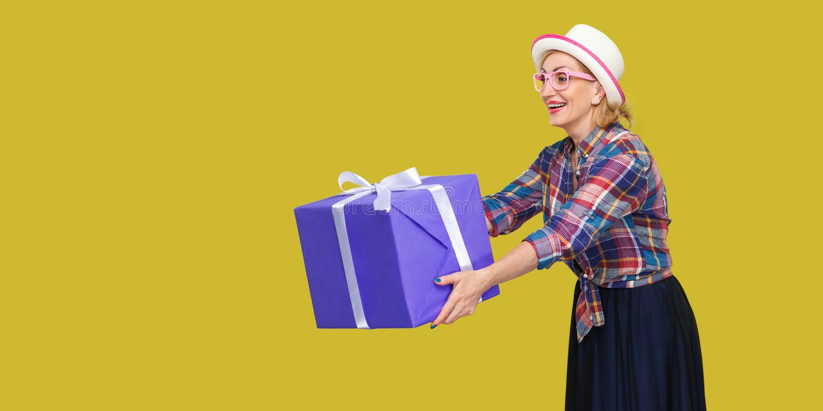 Side view portrait of happy beautiful fancy grandma in white hat and in checkered shirt standind, sharing, giving you big gift box stock image