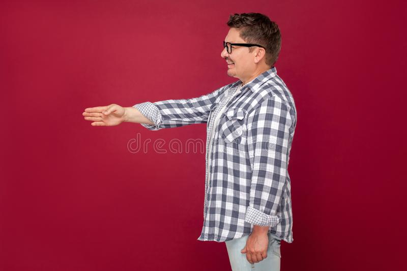 Side view portrait of happy excited middle aged business man in casual checkered shirt, eyeglasses standing, giving hand to stock photos