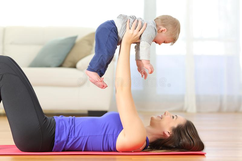 Mother exercising with her baby at home royalty free stock images
