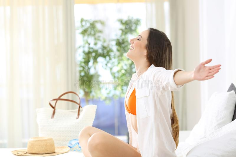 Woman breathing in an hotel room in summer vacations. Side view portrait of a happy oman breathing fresh air sitting on a bed in an hotel room in summer stock photos
