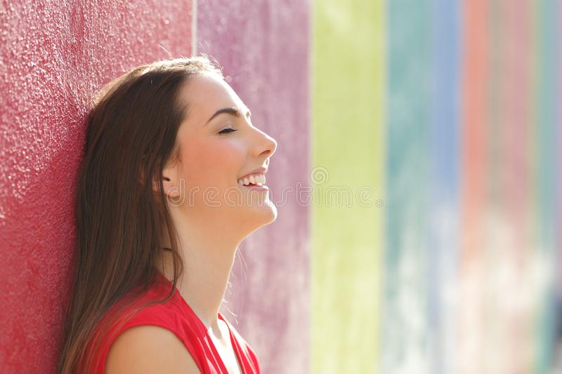 Happy woman resting leaning in a colorful wall royalty free stock image