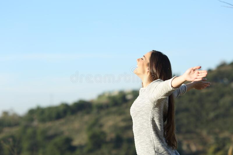 Happy woman stretching arms breathing fresh air royalty free stock image