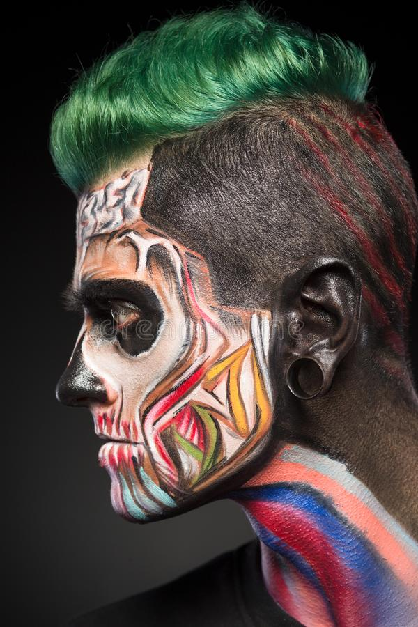 Side view portrait on man with zombie face art in bright colores. royalty free stock photography