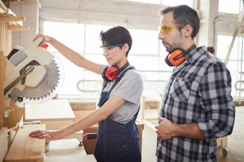 Mature Carpenter Helping Trainee in Workshop stock photos