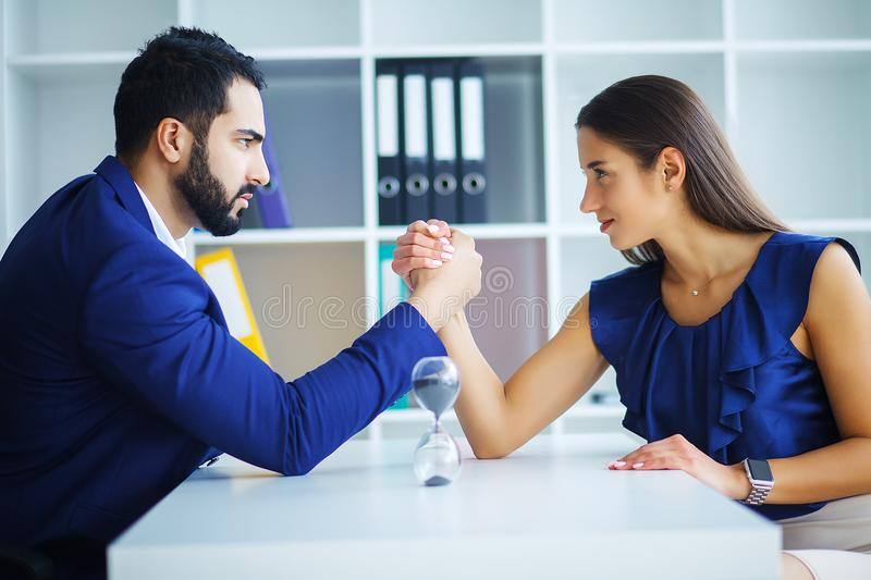 Side view portrait of man and woman armwrestling, exerting press. Side view portrait of men and women armwrestling, exerting pressure on each other, looking eyes royalty free stock image