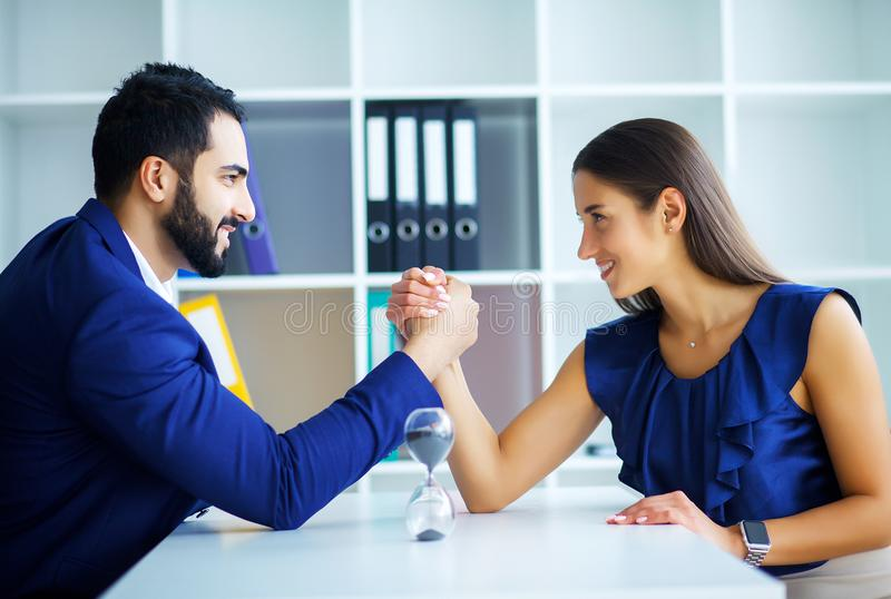 Side view portrait of man and woman armwrestling, exerting press. Side view portrait of men and women armwrestling, exerting pressure on each other, looking eyes stock images