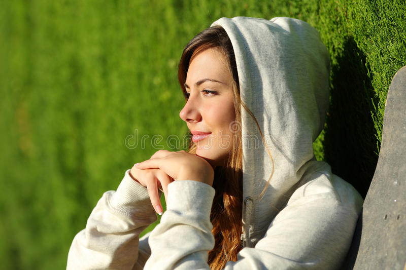 Side view portrait of a pensive teenager skater girl thinking royalty free stock photography