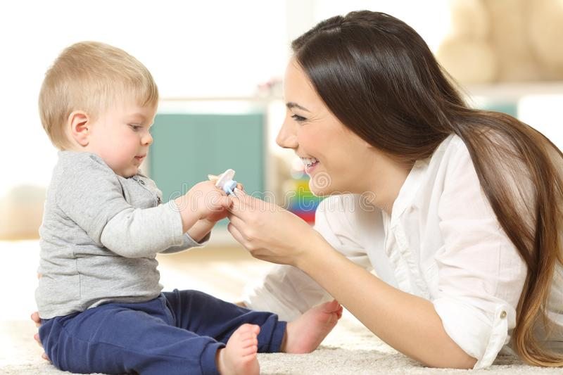 Proud mother giving a pacifier to her baby stock images