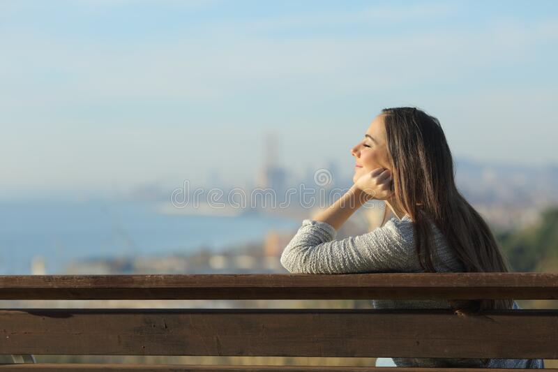 Relaxed woman sitting in a bench with closed eyes royalty free stock photography