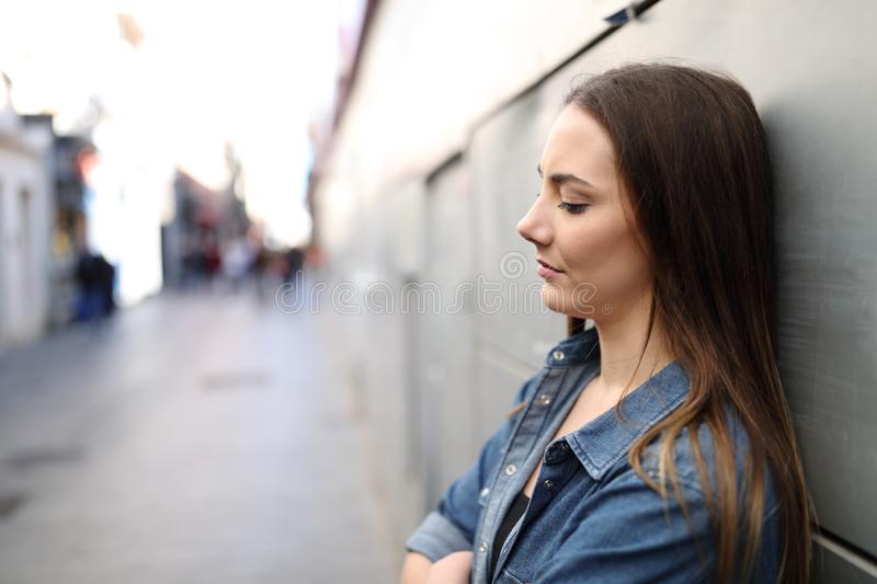 Sad girl complaining leaning on a wall in a solitary street stock photography
