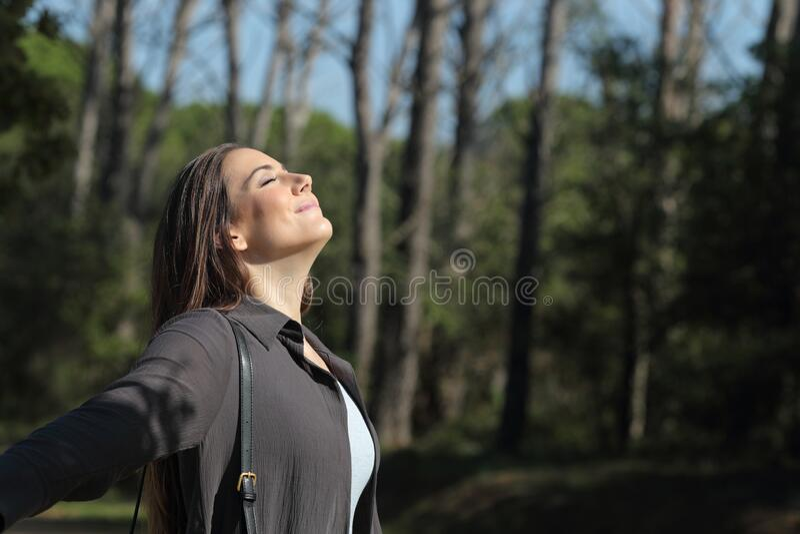 Satisfied woman breathing deeply fresh air enjoying sunshine stock photos
